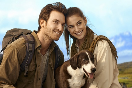 strolling: Happy young couple outing with dog, smiling, looking away. Stock Photo