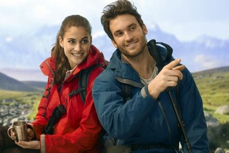 Happy young trekkers sitting and taking rest. Stock Photo