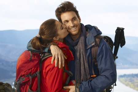 Happy hiking couple on top of the hill, woman kissing man. photo