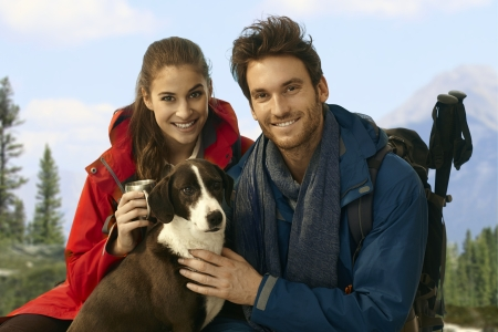 Young happy trekkers with dog taking rest while hiking in mountains. photo