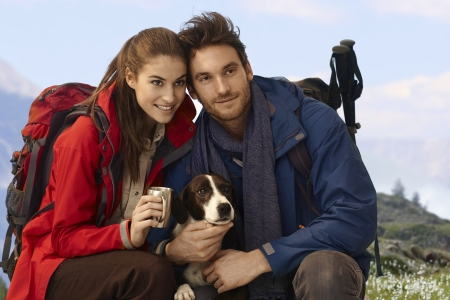 Happy hikers with dog enjoying spring in mountains. photo
