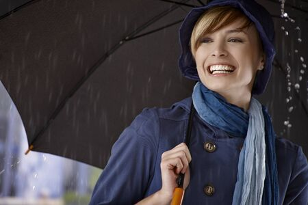 Happy young woman using umbrella in rain, smiling. photo
