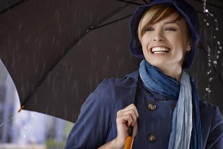gingerish: Happy young woman using umbrella in rain, smiling. Stock Photo