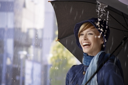enjoy space: Happy young woman standing under umbrella in rain, laughing.