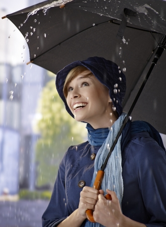 Portrait of happy young woman under umbrella in the rain, smiling. Stock Photo