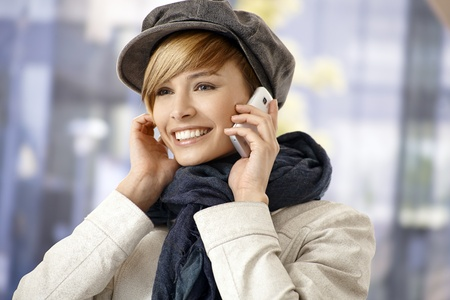 Attractive young woman talking on mobile phone outdoor in wintertime. photo