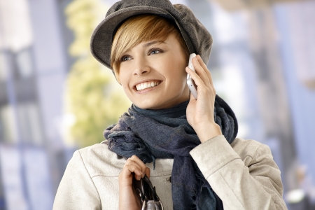Happy young woman wearing winter clothes talking on mobile, outdoors. photo