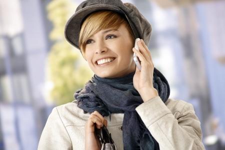 gingerish: Mujer joven feliz vistiendo ropa de invierno hablando por el m�vil, al aire libre.