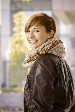 gingerish: Outdoor portrait of young woman wearing leather jacket in spring sunshine Stock Photo