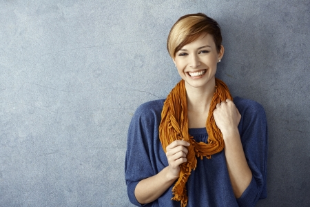 Portrait of young woman smiling happily standing by wall. Copy space. Stock Photo