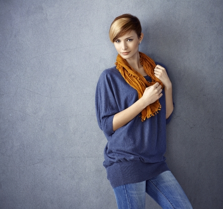 gingerish: Portrait of attractive young woman leaning to wall, smiling. Stock Photo