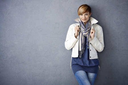 Attractive young woman in white jacket and scarf standing by grey wall photo