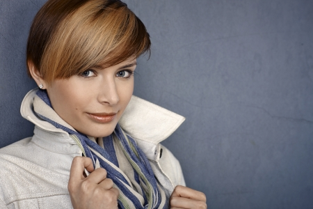Attractive young woman in jacket and scarf over grey background photo