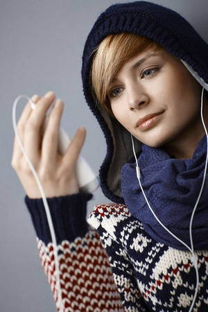 Hooded young woman listening music, looking at player Stock Photo - 22070812