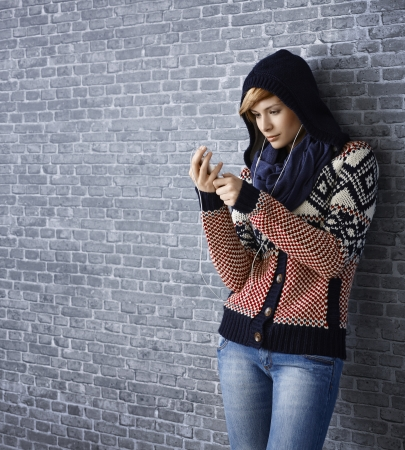 gingerish: Attractive young woman leaning to wall using mp3 player Stock Photo