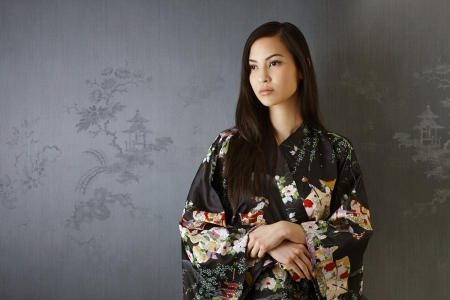 Portrait of Japanese woman in traditional kimono standing by grey wall, looking away. photo
