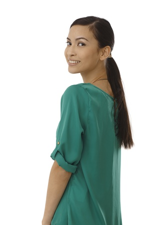 Attractive young woman looking over shoulder, smiling in green blouse. photo