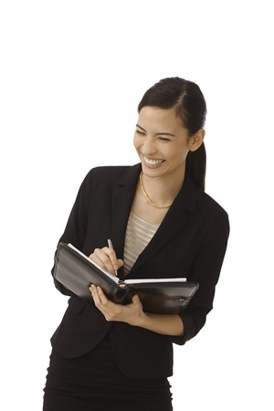 personal assistant: Young secretary making notes to personal organizer, smiling happy. Stock Photo