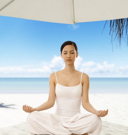 Beautiful woman practicing yoga on the beach, sitting eyes closed, meditating, relaxing. photo