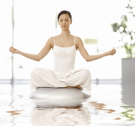 tailor seat: Young woman sitting in yoga position, relaxing eyes closed.
