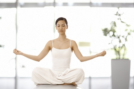 Beautiful young woman practicing yoga, relaxing eyes closed. photo