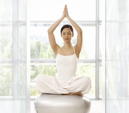practicing: Young woman sitting in prayer position, practicing yoga indoors. Stock Photo