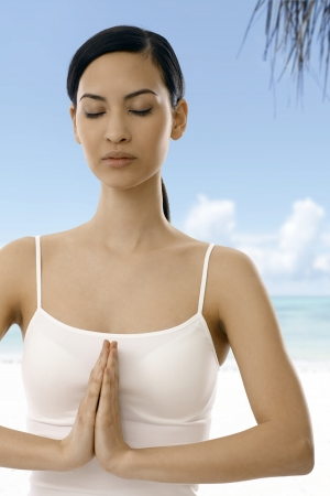 Attractive woman practicing yoga eyes closed open air, prayer position. photo