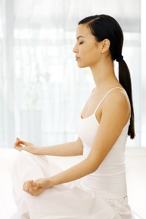 Side view of young woman practicing yoga indoors, relaxing eyes closed. photo