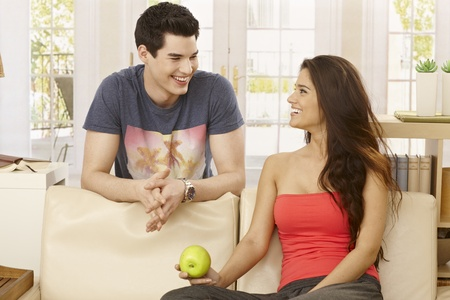 Happy young couple talking in living room at home, smiling. photo