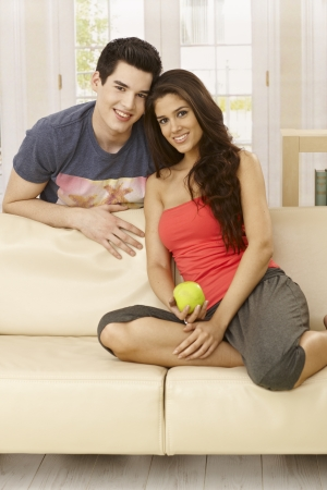 couple couch: Young loving couple in living room at home, smiling happy.