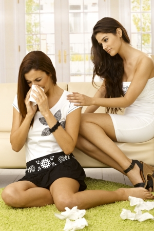 Young woman sitting on carpet crying, friend consoling her. photo