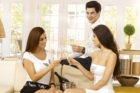 compa�erismo: Compa��a joven y feliz celebrando con champ�n en el hogar, gafas chocan, sonriendo.