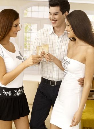 amigos abrazandose: Mujer joven felicitaron joven pareja en el compromiso, tintineo de vasos, celebrando con champagne. Foto de archivo
