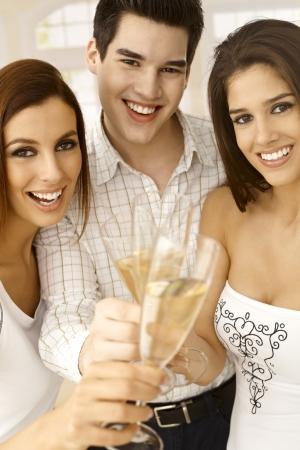 compa�erismo: Compa��a joven celebrando con champ�n, vasos tintineando, sonriendo feliz. Foto de archivo