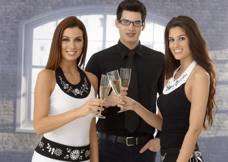 Young friends celebrating with champagne, clinking glasses, wearing black and white, smiling happy.