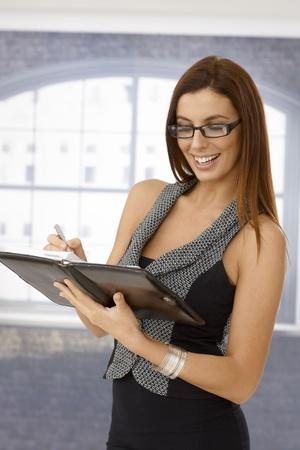Pretty secretary holding personal organizer, writing notes, smiling. photo
