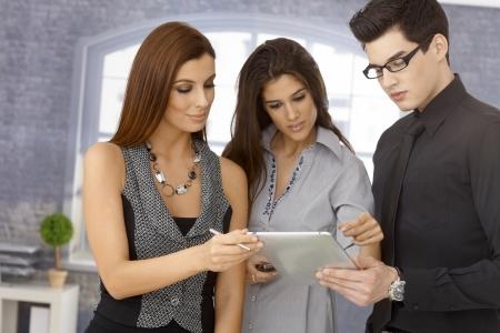 cooperating: Young businesspeople working together, using tablet computer.