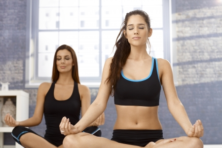 tailor seat: Attractive young women sitting in tailor seat eyes closed, practicing yoga, meditating. Stock Photo