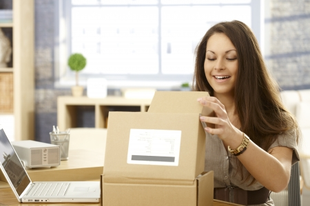 open box: Young woman sitting at table, opening postal packet, smiling happy.