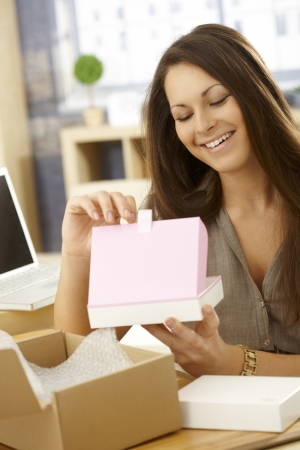 Happy young woman opening parcel, looking at gift box, smiling happy. Imagens