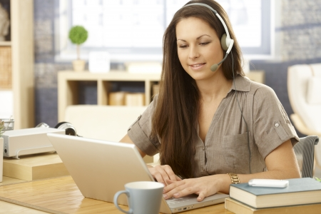 good work: Young woman using laptop computer at home, wearing headset. Stock Photo