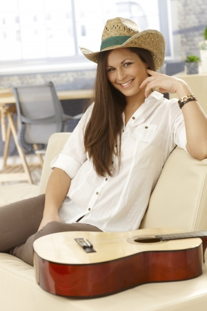 Young female guitar player sitting on sofa at home, smiling happy, instrument lying by her.