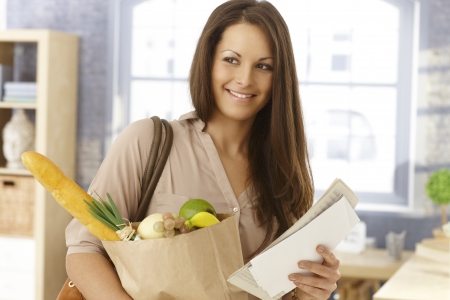 arriving: Happy woman arriving at home with shopping bag and mail, smiling. Stock Photo