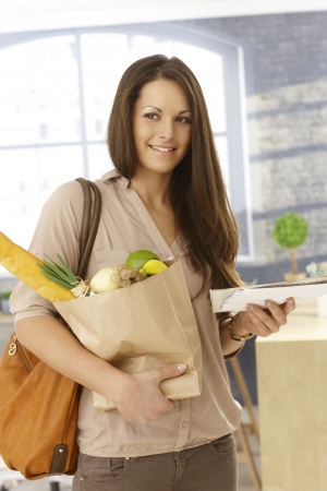 arriving: Young woman getting home, holding shopping bag and mail, smiling happy. Stock Photo