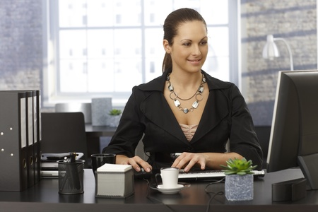 Young businesswoman sitting at desk in office, working on computer, smiling. photo