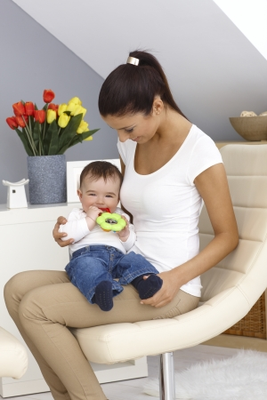 Pretty young mother holding baby boy on lap. Baby playing with toy. photo