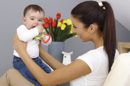 babyboy: Young mother playing with baby boy, holding him on lap, smiling happy. Baby holding toy. Stock Photo