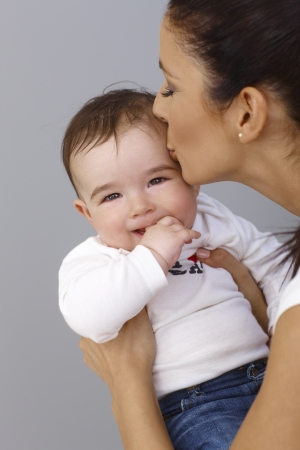kissing mouth: Mother kissing baby boy affectionately. Baby smiling with thumb in mouth.