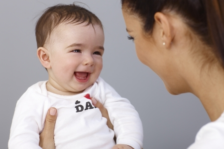 Happy baby boy laughing in mothers arms. photo