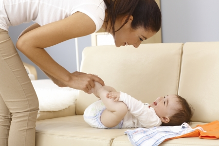 babyboy: Young mother and baby boy having fun while dressing up on sofa. Stock Photo